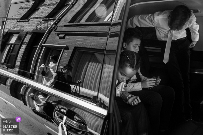 Brick buildings are reflected in a car door as children prepare to exit the vehicle at De Lelie, Veurne in this black and white photo by an Antwerpen, Flanders wedding photographer.