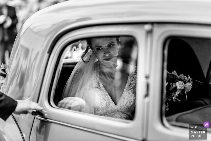 Die Braut bereitet sich darauf vor, ihr Fahrzeug für die Zeremonie in Ploemeur, Frankreich, in diesem preisgekrönten Schwarzweißbild eines Hochzeitsfotografen aus Melbourne, Australien, zu verlassen.