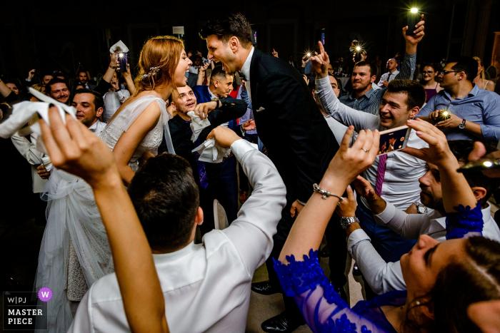 Rumänien Hochzeitsfotografie | Foto gemacht während der Party, wo der Bräutigam und die Braut auf den Stühlen standen, vor allen