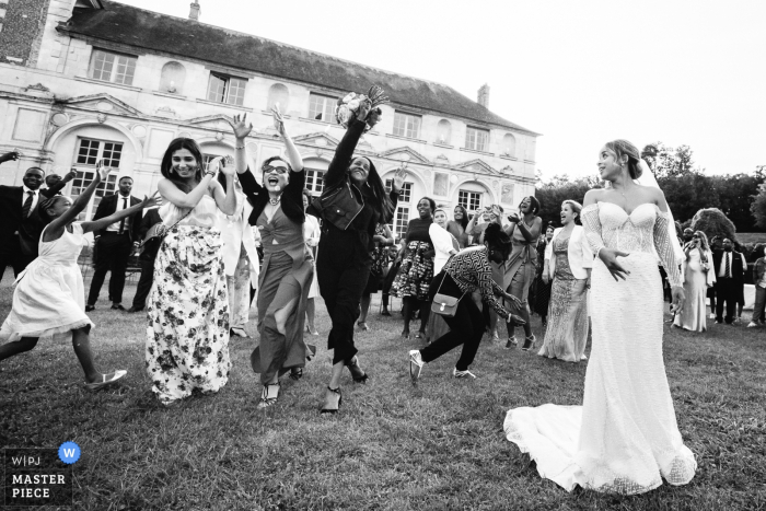 Guests fight to catch the bride's bouquet at the Chateau Valery in this black and white wedding image composed by an award-winning Paris, France photographer.