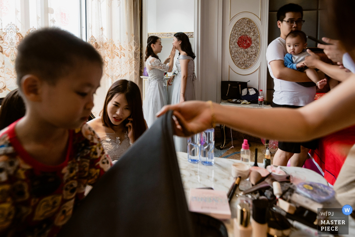 The room is full of people getting themselves ready for the ceremony in this award-winning image composed by a Sanming, China wedding photographer.