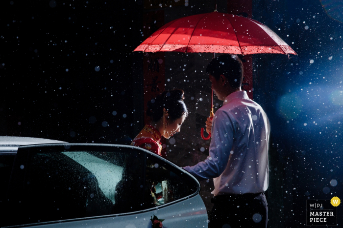 A man holds an umbrella over the bride as she steps out of her car and into the snowy night in this documentary-style photo by a Fujian, China wedding photographer.