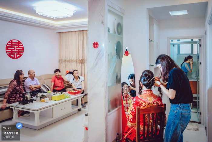 The bride gets her hair done while her family waits in the other room in this award-winning photo by a Fujian, China wedding photographer.