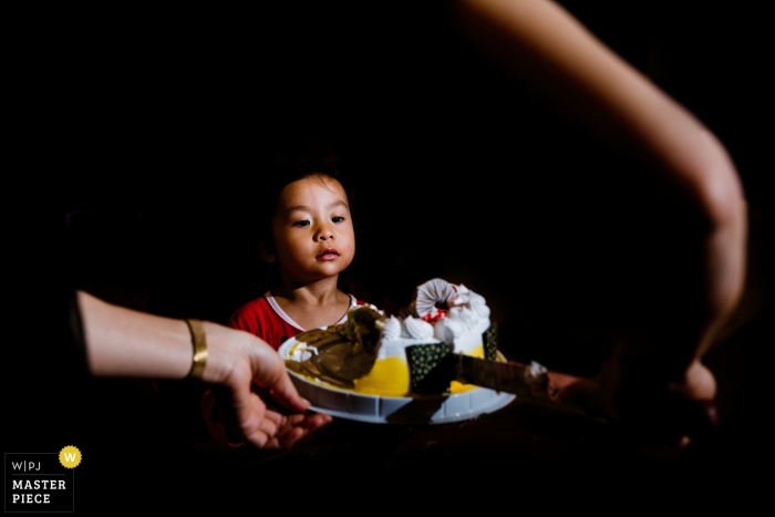 A little boy looks at the large plate of food being placed in front of him in this image captured by a Fujian, China, wedding photographer.