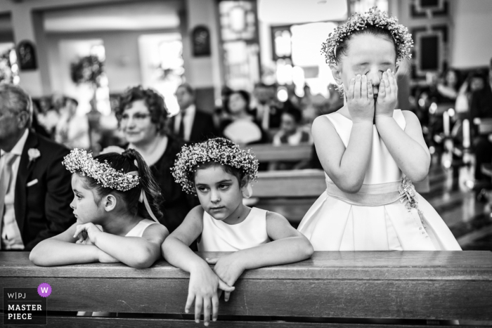 A girl covers her face while two others watch the ceremony in Lettere in this black and white photo by a Naples, Campania wedding photographer.