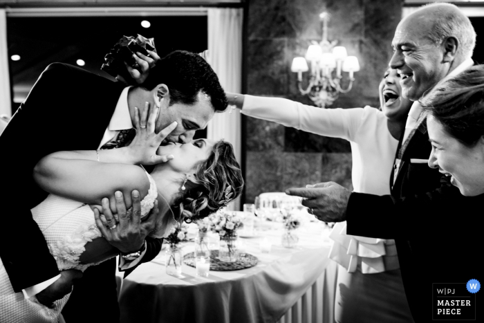 Guests smile and cheer as the groom kisses the bride during their reception at El Puig in this black and white image composed by an award-winning Valencia, Spain wedding photographer.