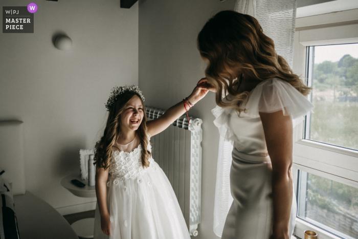 Die Braut hebt den Arm des Blumenmädchens, um sich vor ihrer Hochzeit im Le Chiacchiere Artena ein Bild von ihrem Kleid zu machen.