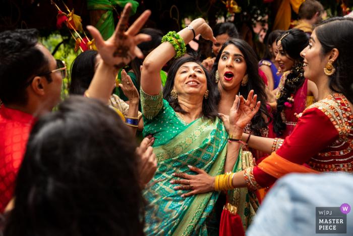 Die Braut und die Gäste tanzen und feiern eine traditionelle indische Hochzeit in Toskana in diesem Hochzeitsbild, das von einem Florenz-Fotografen hergestellt wird.