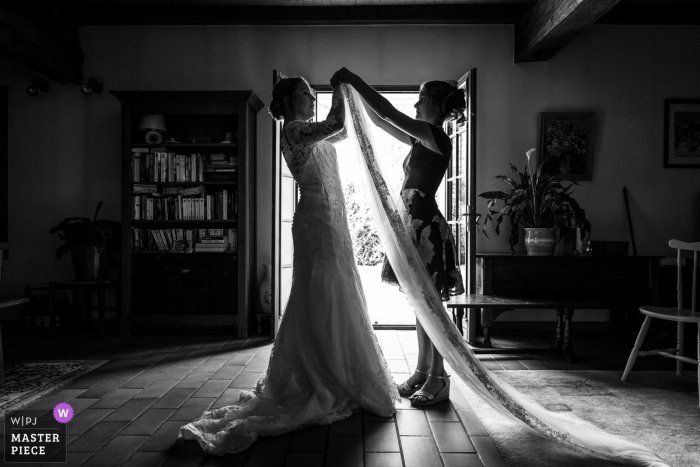 The bride's sister helps her with her veil before her wedding at Neuville-aux-bois in this black and white photo by an award-winning Centre-Val de Loire, France wedding photographer.