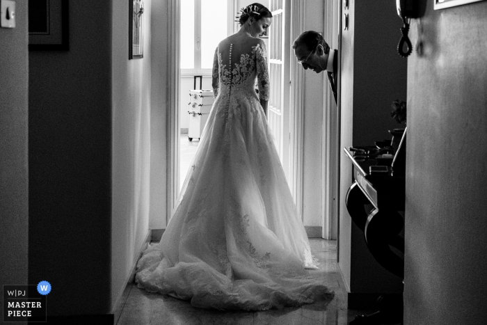 A man examines the bride's gown before her wedding at San Francesco all'Immacolata in this black and white photo by a Catania, Sicily photographer.