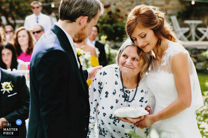 Castello di Rosciano Wedding Ceremony Photo of the Grandmother bringing the rings outdoors