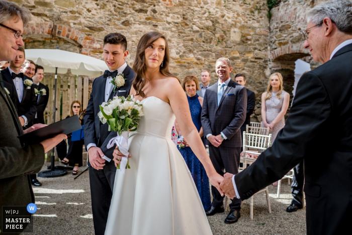 Hochzeitszeremoniephotographie Wilton Castle, Irland, welche die Übergabe durch den Vater der Braut an den Bräutigam zeigt