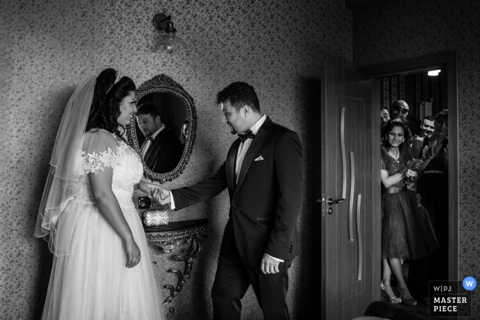 The bride and groom hold hands in the NDK in Sofia as guests watch in this black and white wedding image captured by a Bulgaria photographer.