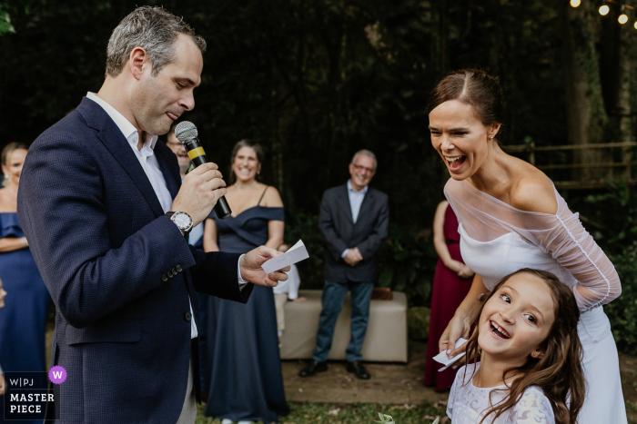 Die Braut und ein kleines Mädchen lachen, als ein Mann während dieser Hochzeit in der Casa dos Novios eine Rede eines preisgekrönten Fotografen aus Porto Alegre hält.