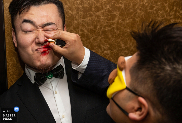 A blindfolded man tries to put red lipstick on another during a game in this photo by a Beijing, China wedding photographer.