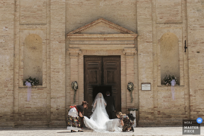 Two women help the bride arrange her beautiful dress as she prepares to enter the ceremony at Chiesa Santa Croce Mogliano in this image created by a Macerata, Marche wedding photographer.