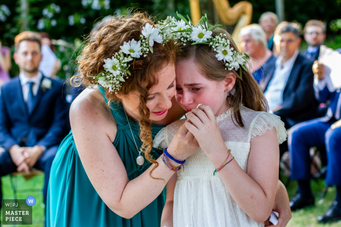 A woman wipes the tears of a crying little girl during the ceremony at I Giardini di Villa Fago, Santa Venerina in this documentary-style image composed by a Catania, Sicily wedding photographer.