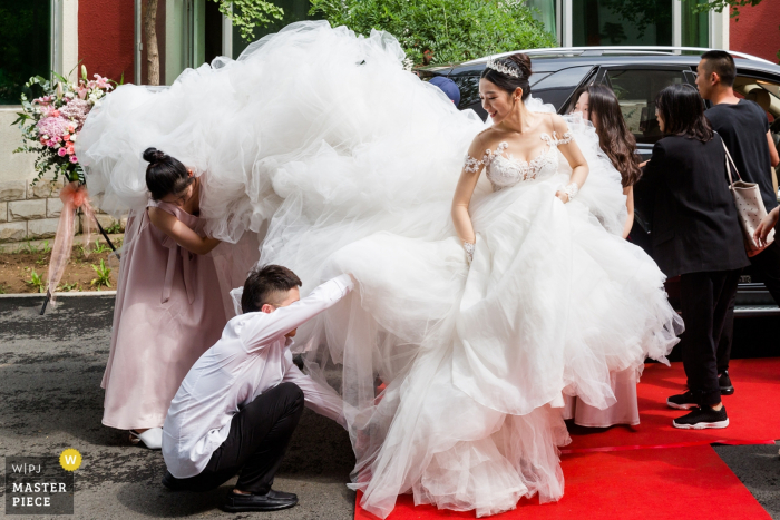 A few guests try to help the bride with her gigantic wedding dress outside of Beijing Yunheyuandujiacun Hotel in this award-winning wedding image by a Beijing, China photographer.