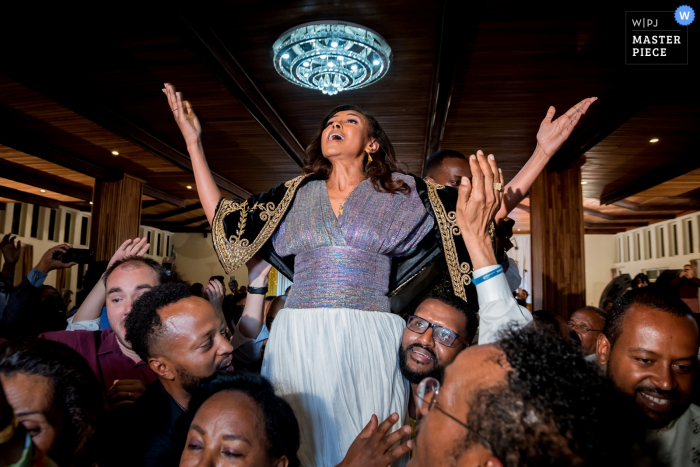 Guests lift up the bride during the reception at Addis Ababa in this photo by a Toronto, Ontario wedding photographer.