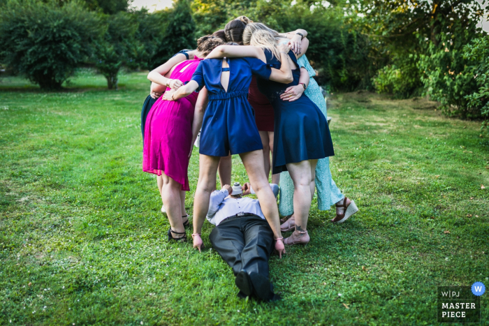 Women huddle together as a man lays on the ground and takes a picture of them from below in this award-winning photo composed by a Paris, France wedding photographer.