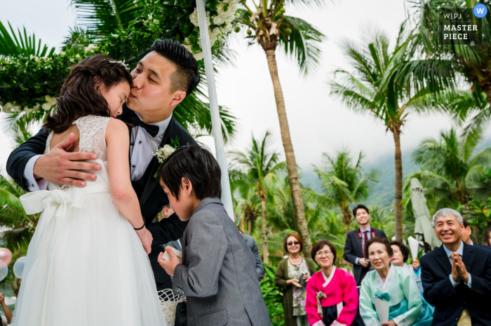 The groom hugs his children during his Da Nang wedding ceremony.