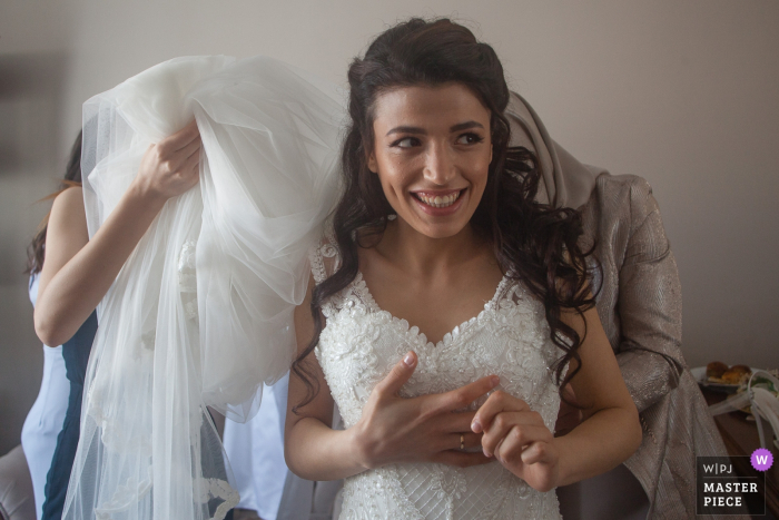 Istanbul - Fatih Evlendirme Dairesi Photography - Bride looking excited as the unknown women helping her with the wedding dress