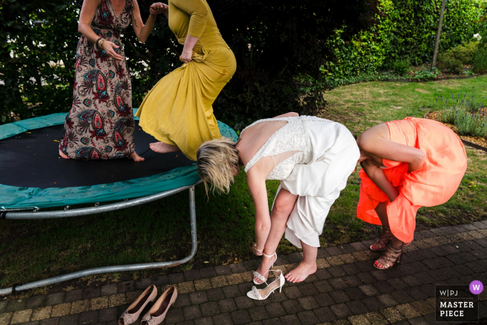 Two women take their shoes off to join two others on a trampoline in Spiegeltent Glabbeek in this award-winning photo by a Flanders, Belgium documentary-style wedding photographer.