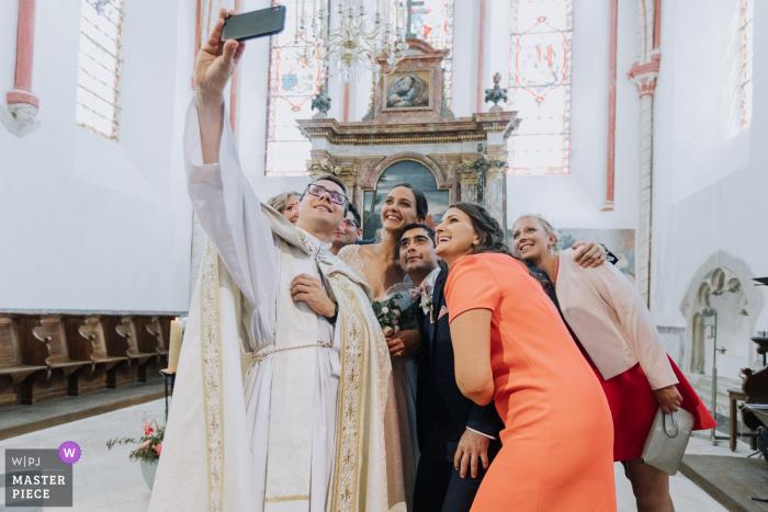 Der Priester macht ein Selfie mit der Brautparty in der Kirche von La Chatelet En Brie auf diesem Bild, das von einem preisgekrönten Hochzeitsfotografen aus Morbihan, Bretagne, aufgenommen wurde.