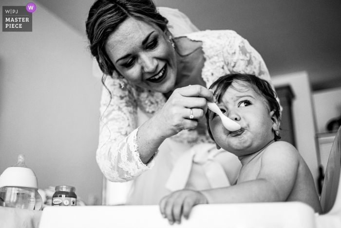 The bride feeds a concerned-looking baby at Le Lavandou in this black and white award-winning image by a Marseille wedding photographer.