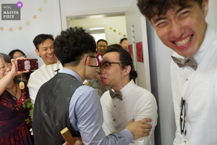 Guests laugh as two men play a game in Changsha in this documentary-style wedding picture composed by a Hunan, China photographer.