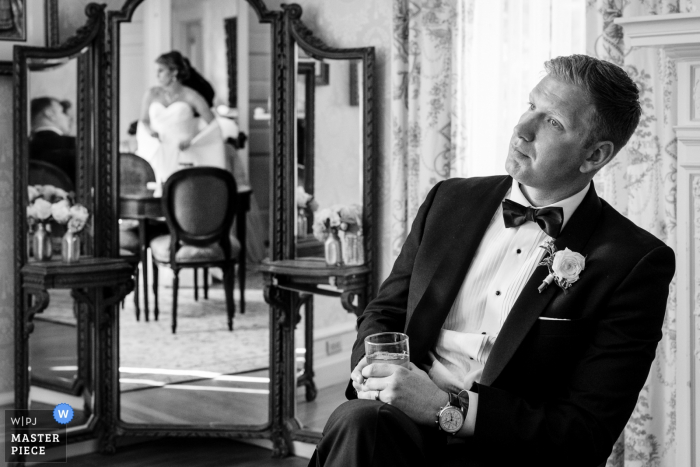 Glencairn Mansion Wedding Venue Photographer - The groom looking on as the bride gets her dress bustled.