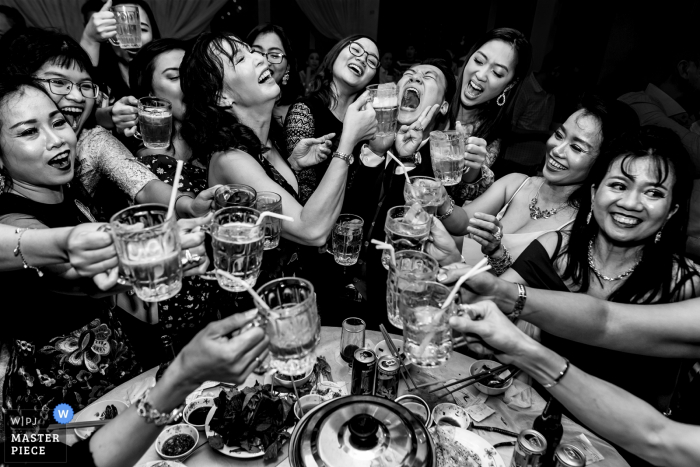 A group of guests with only one guy share drinks together at Zenna Restaurant in this black and white photo by a Ho Chi Minh, Vietnam wedding photographer.