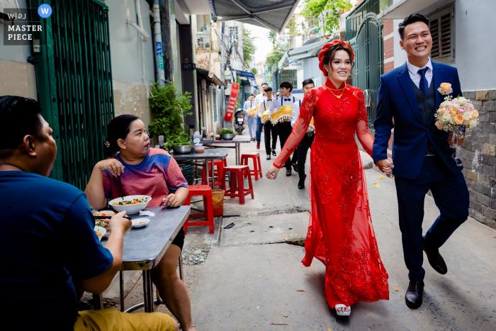 Les mariés se tiennent la main alors qu'ils sont suivis par une procession alors qu'ils rentrent chez eux dans cette image de style documentaire capturée par un photographe de mariage à Ho Chi Minh, au Vietnam.