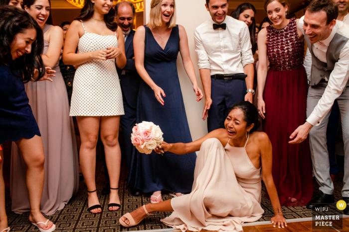 Todos se ríen cuando una invitada trata de ponerse de pie después de que ella se cayera tratando de recoger el ramo en el hotel Palo Alto Garden Court en esta imagen de boda compuesta por un fotógrafo de San José, California.