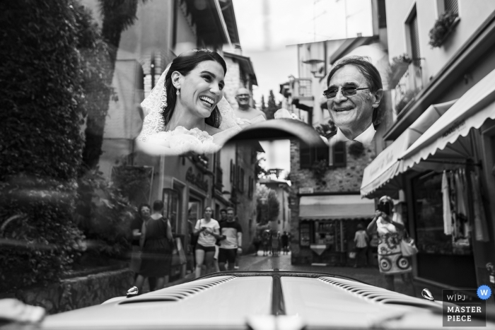 Garda Island - Italy Wedding Photographer. On the way to the church by car. A smile between the bride and the father reflected in the mirror, among the streets of sirmione.
