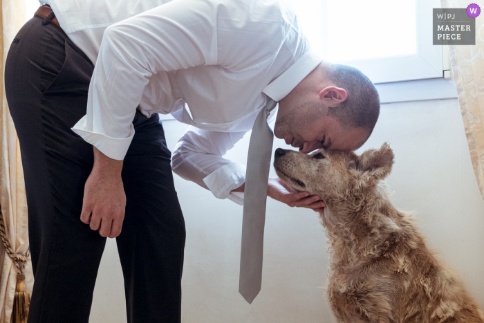 The groom gives his dog a hug before the ceremony in Chaptelat in this image captured by a Nouvelle-Aquitaine, France wedding photographer.