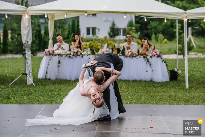 The groom dips the bride nearly down to the floor in this documentary-style photo by a Sofia, Bulgaria wedding photographer.