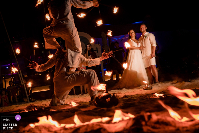 The bride, groom, and guests enjoy a fire dance show at night in this documentary-style wedding image composed by a Phuket, Thailand photographer.