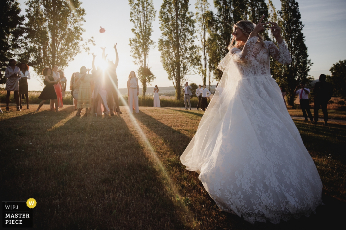 The bride tosses her bouquet over her shoulder as the sun sets at Clos de L'Orangerie Rosney Sur Seine in this documentary-style wedding photo by an award-winning Paris, France photographer.