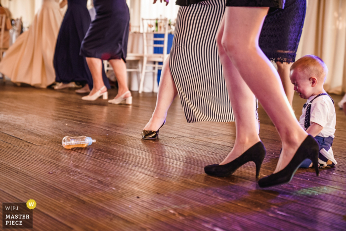 A baby boy stares longingly at his bottle that has rolled onto the dance floor at Villa Ekaterina in this image composed by a Sofia, Bulgaria wedding photographer.