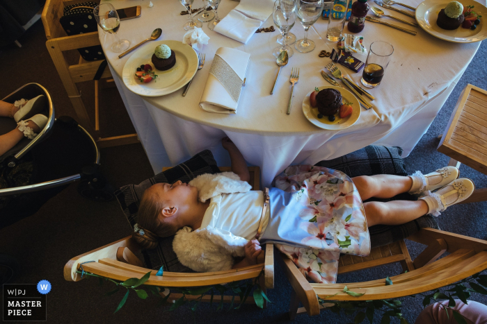 Wedding Photography at The Gardens, Yalding - flowergirl asleep at the table