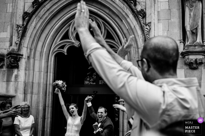 The bride and groom exit their ceremony in Brugge with their arms raised in this black and white picture captured by an Antwerpen, Flanders documentary-style wedding photographer.