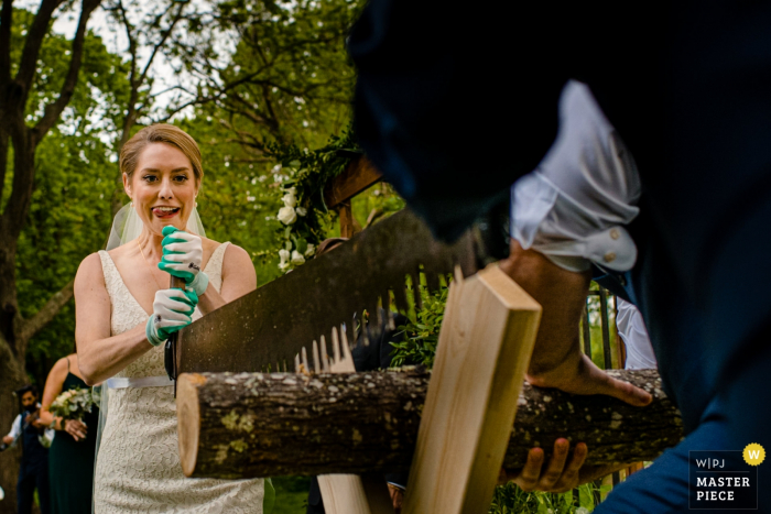 Hubbard Park Shorewood Wisconsin Wedding Photo showing the Bride and Groom do a sawing tradition - Madison, WI photographer