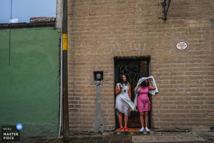 Palisandro San Miguel de Allende, México Fotografía | Los invitados a la boda esperan la lluvia repentina y el viento para detenerse en la acera.