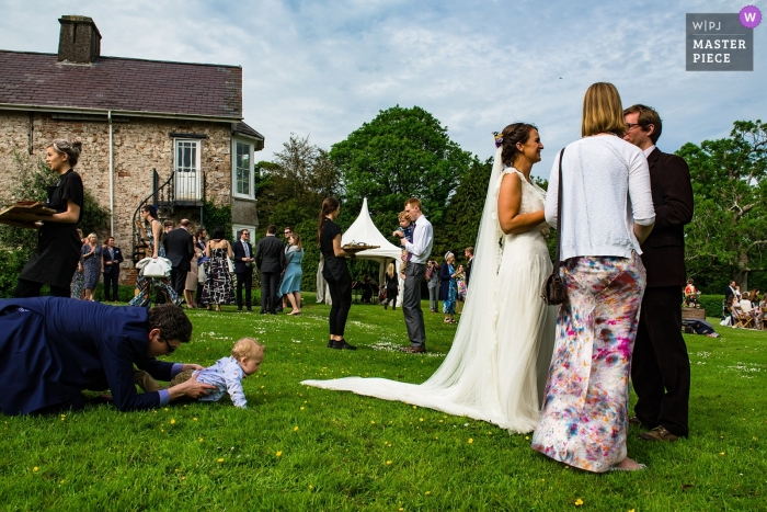 Penmaen House, Wales reception party on the lawn | Crawling baby makes an attempt to escape toward the bride's dress.