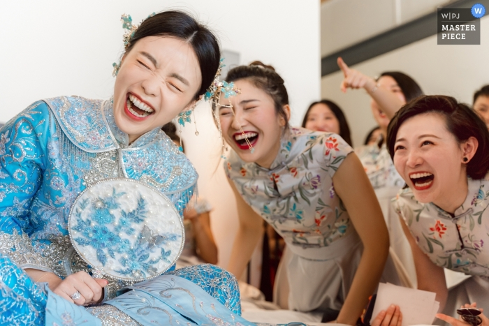 The bride and the bridesmaids were laughing out loud at the funny performance of the groom and the groomsmen at the door game section, at Sava Beach Villas in Thailand.