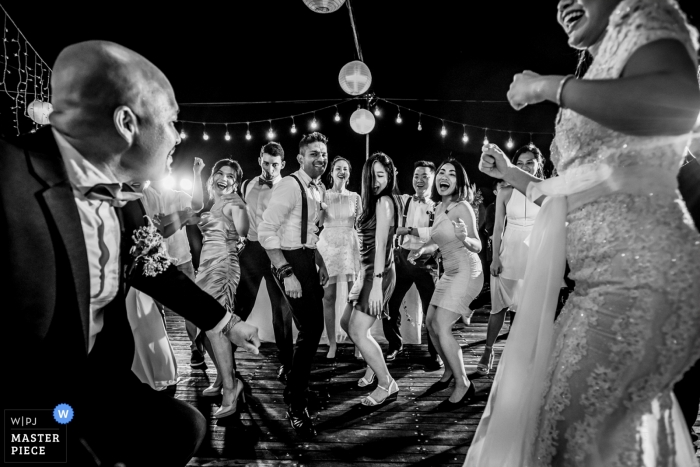 Black and white wedding recepition image from Vietnam of the bride and groom with guests dancing.