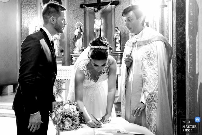 A moment of signatures after the wedding ceremony at Igreja Matriz Nossa Senhora da Conceição  where the priest looked at the bridegroom and said something.