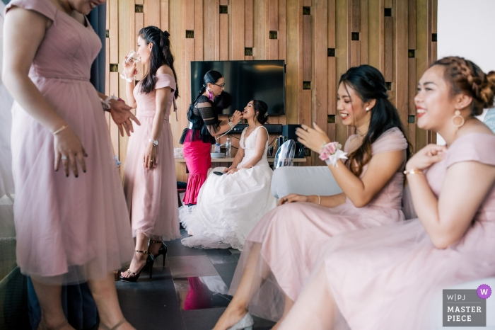 Bridesmaids have a great time together as the bride has makeup applied at Impiana Private Villas in Kata Noi
