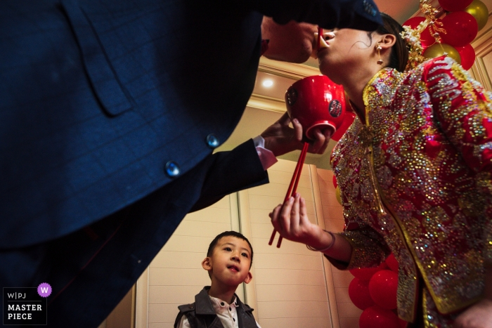 Chinese wedding tradition of bride and groom eating noodles as young boy watches intentively in Liaoning, China